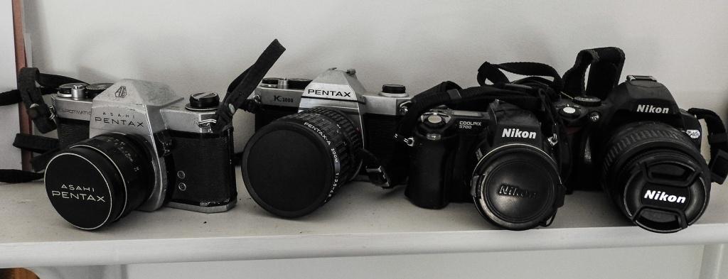Four cameras - a Pentax Spotmatic, a Pentax K1000, a Nikon E5700 and a Nikon D40x.
